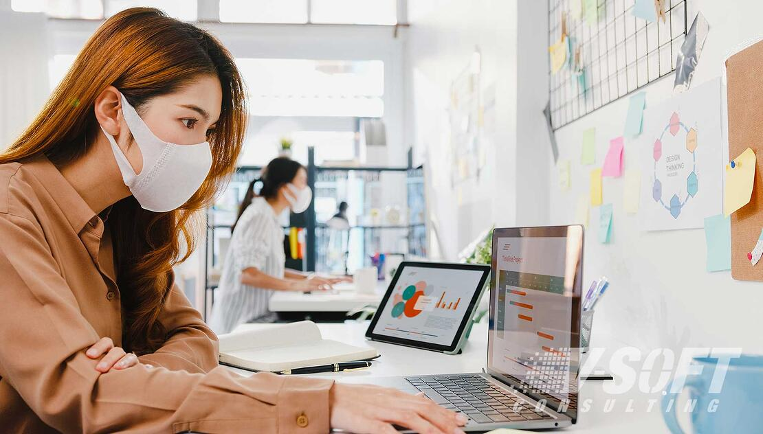 Women working at desks in office while wearing masks