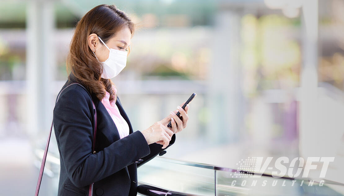 Woman with mask takes self-certification survey via mobile device upon entering the workplace