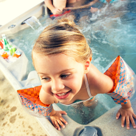 little girl in floaties in hot tub