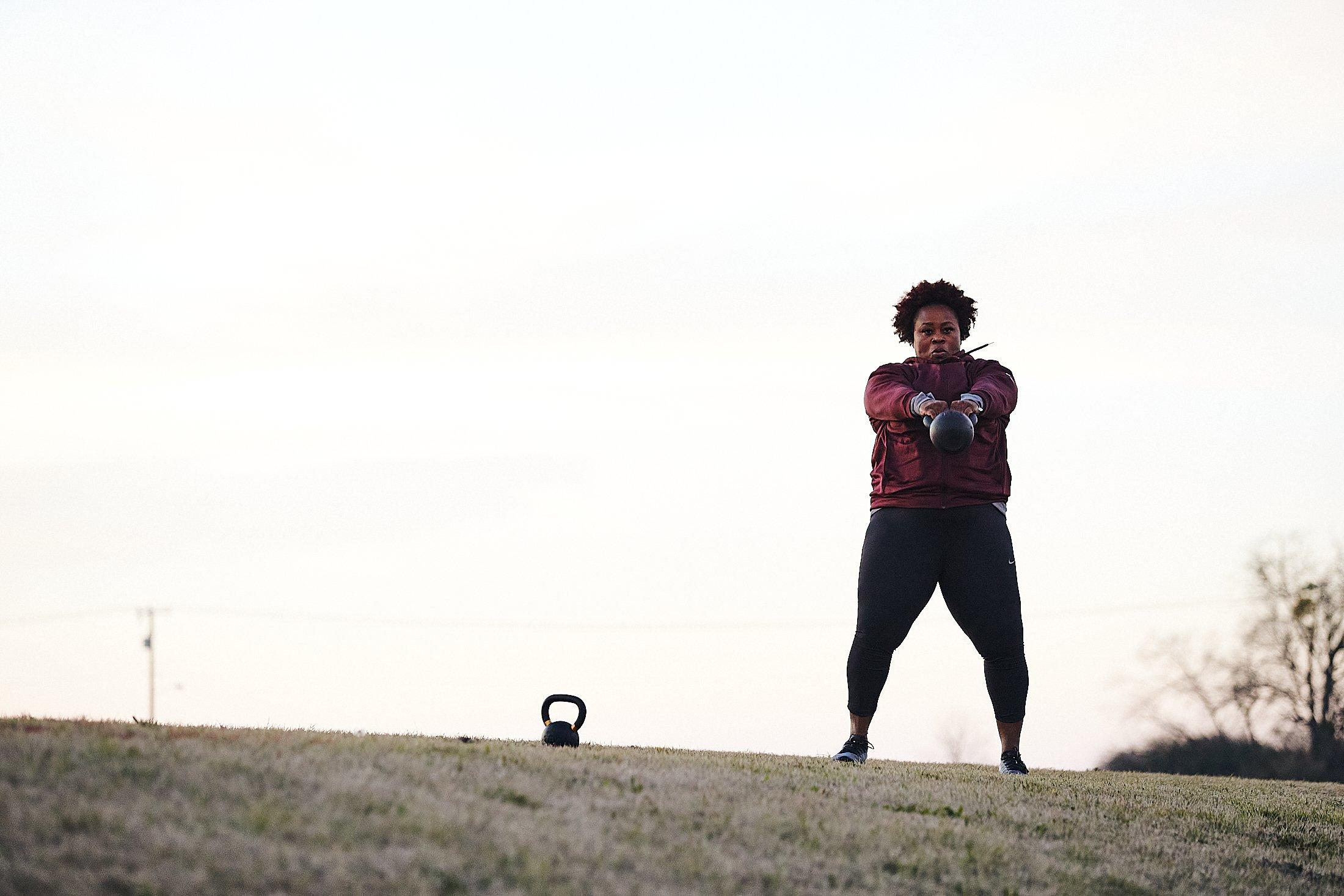 Michelle Carter, wearing a purple longsleeve shirt and black leggings, swings a kettlebell.