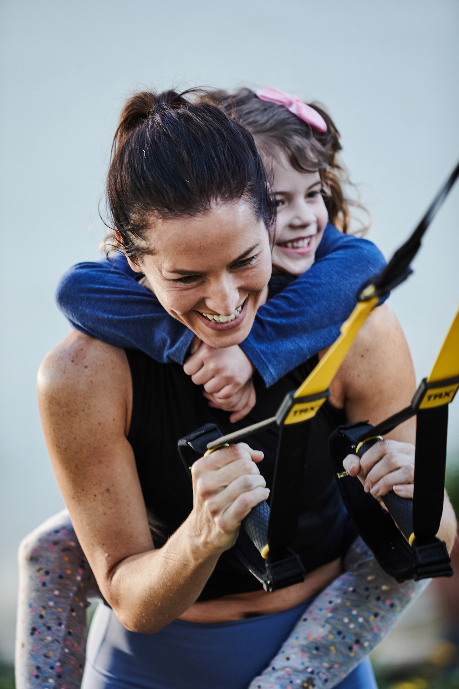Kristin Leffel performs a TRX squat with one of her children hanging on her back