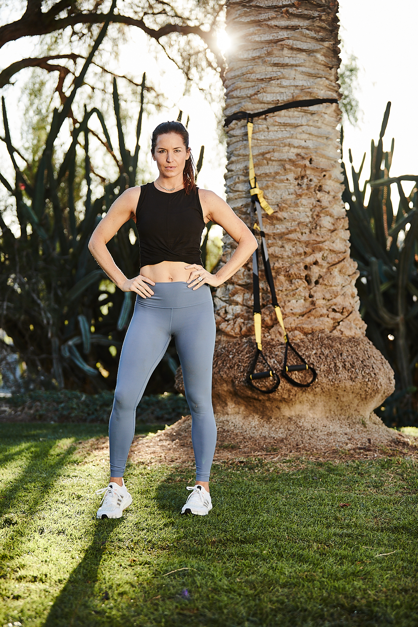 Kristin Leffel, wearing a black crop top and grey leggings, stands in front of a palm tree. Her TRX Suspension Trainer is hanging on the tree behind her.