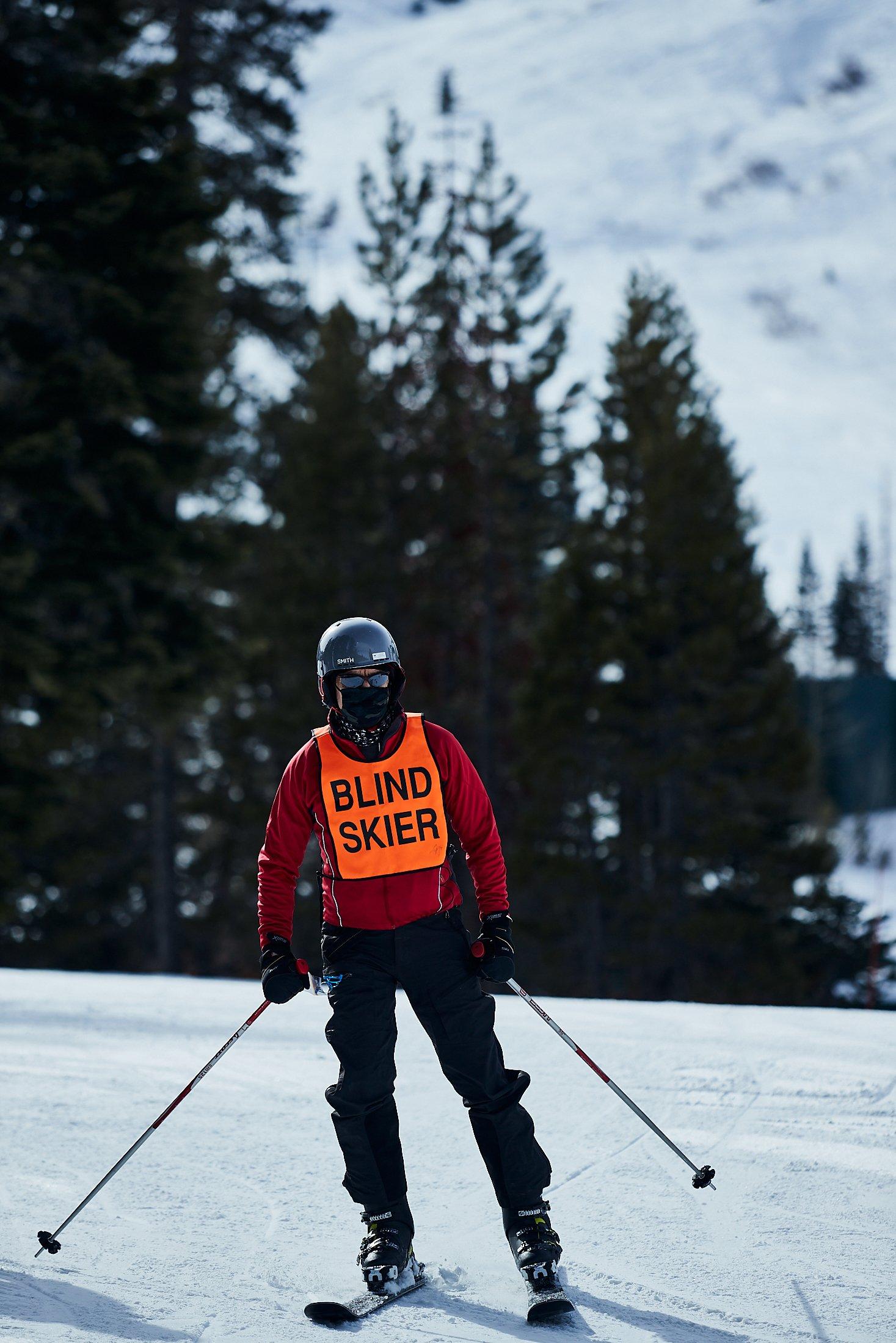 Walt Raineri, wearing a longsleeve red top, black ski pants, and a blind skier vest, skis in Lake Tahoe.