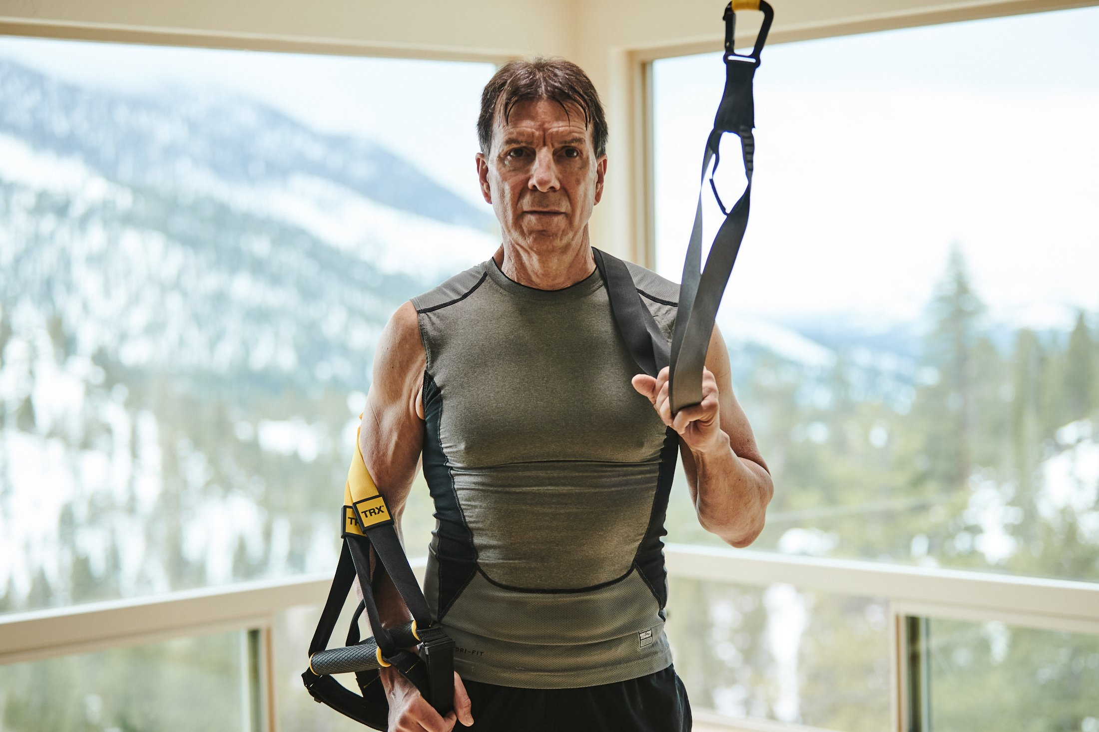 Walt Raineri, wearing a grey sleeveless shirt and black shorts, holds his TRX Suspension Trainer. He's in front of a window, with snow-capped mountains outside.
