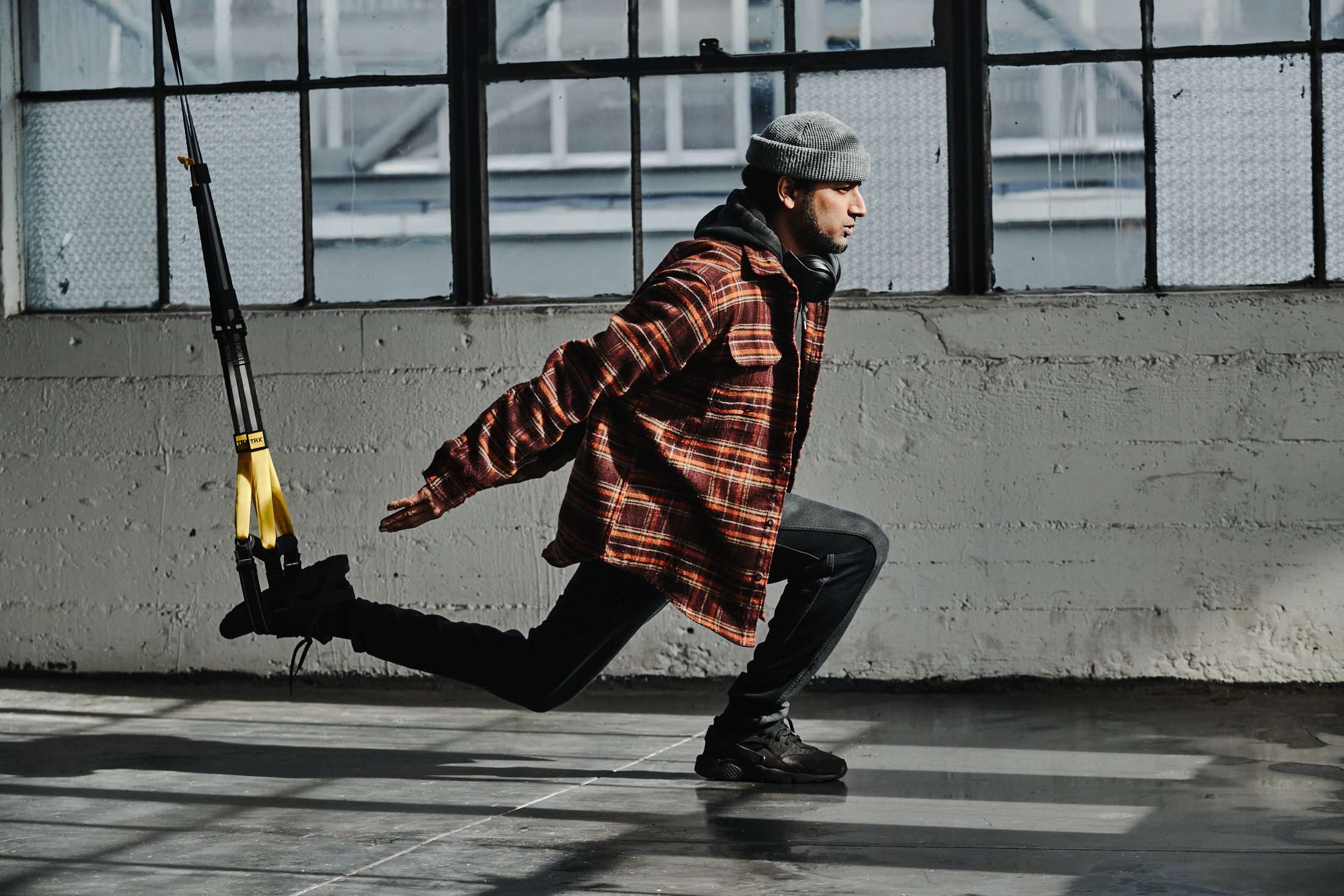 TJ Yale, wearing a beanie, red flannel shirt, and black pants and sneakers, performs a TRX Lunge.