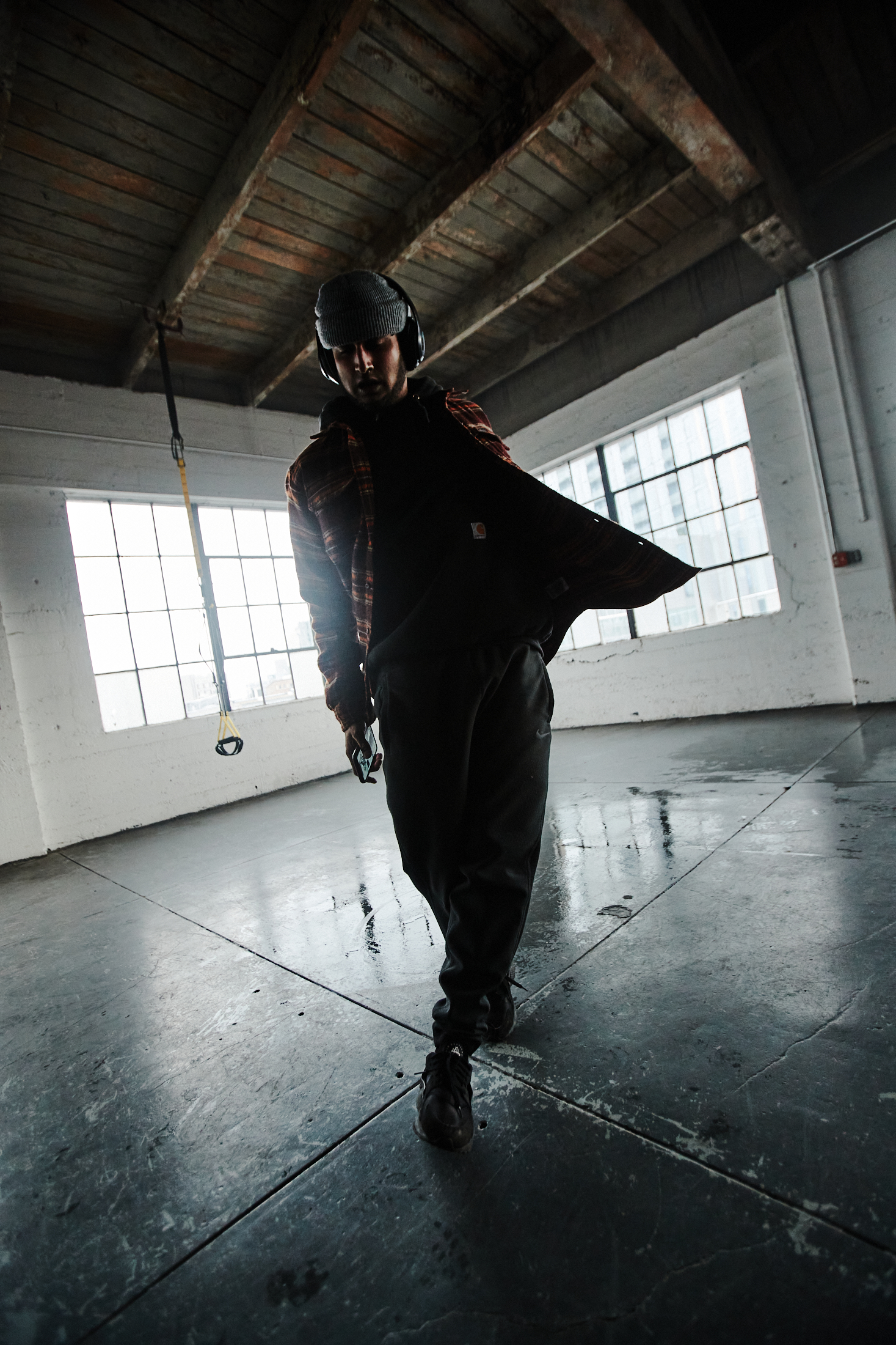 TJ Yale, wearing a beanie, flannel shirt, pants, and sneakers, performs a dance move in an industrial space with windows behind him.