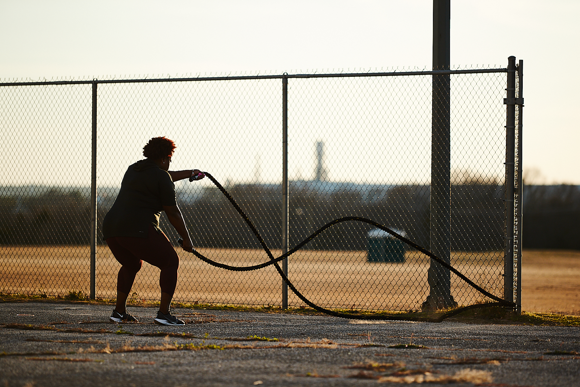 Michelle Carter, in silhouette, trains outdoors with TRX battle ropesith