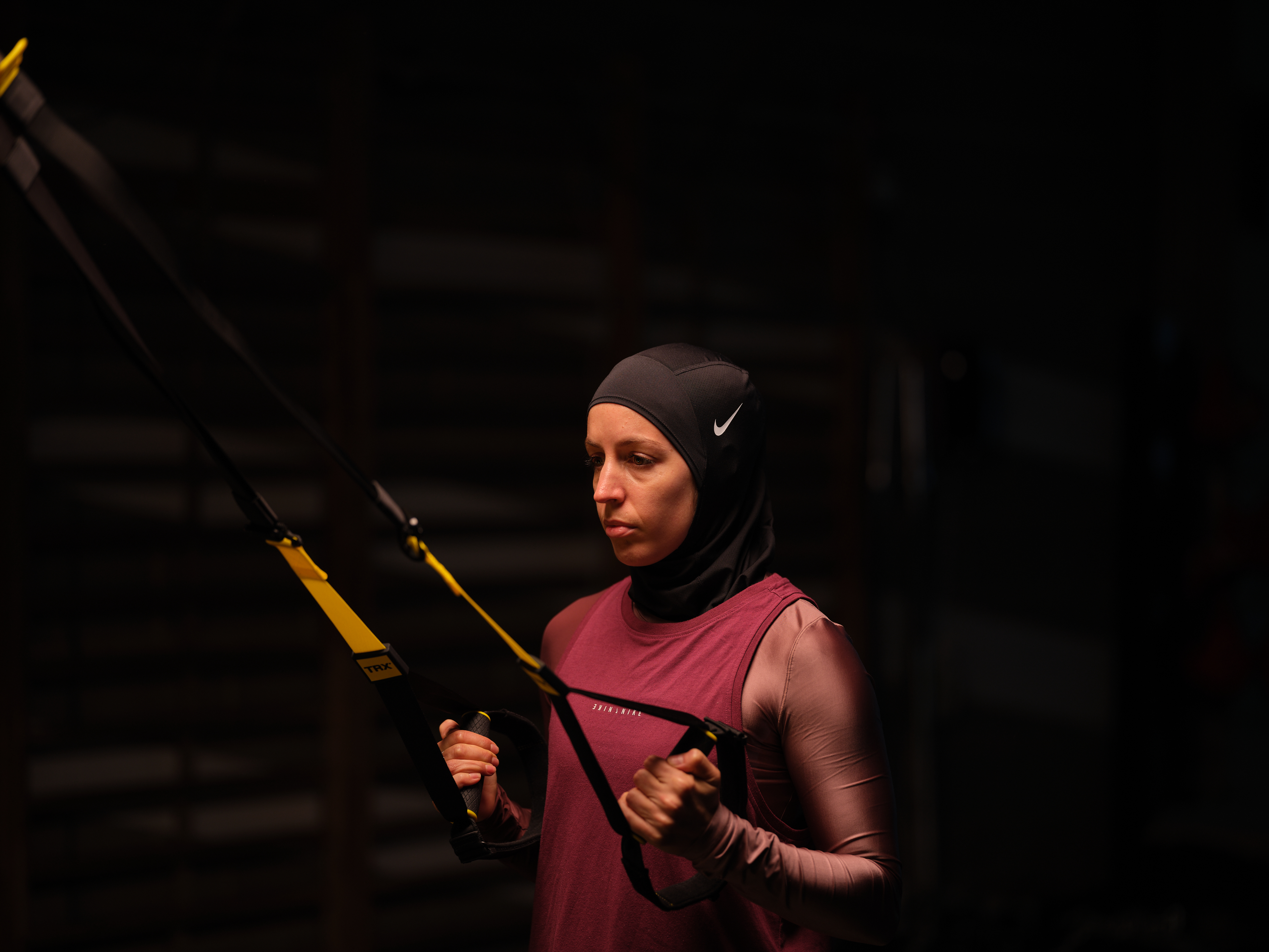 Nesrine Dally using the TRX Suspension Trainer for a TRX Row. She wears a black hijab, pink longsleeve shirt, and dark rose vest.