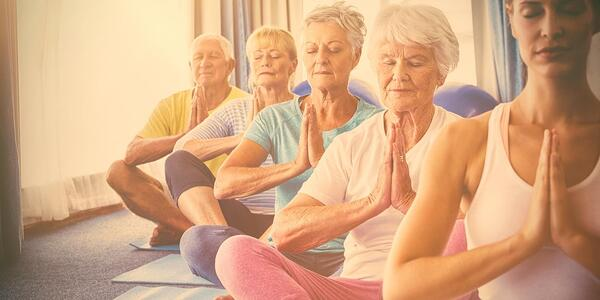 Elderly people with limited mobility doing yoga as a fun activity.