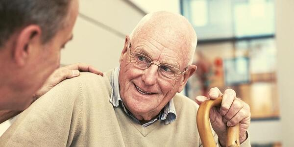 An elderly parent, a gentleman, with dementia that is smiling and talking with his in-home carer in the familiar and comfortable surroundings of his own home.