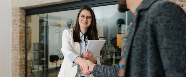 Young business professional shaking hands with another business professional