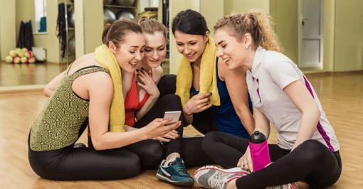 Gruppo di ragazze controllano instagram durante una pausa in palestra