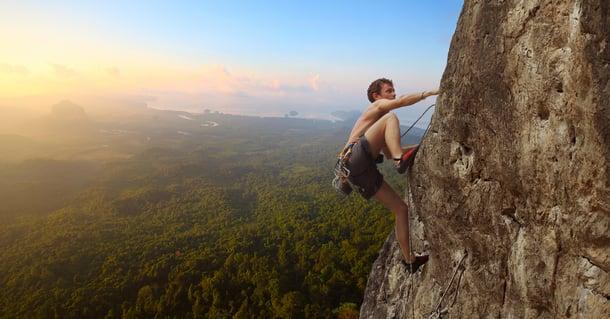 Uomo si arrampica su una parete rocciosa_ concetto di rischio