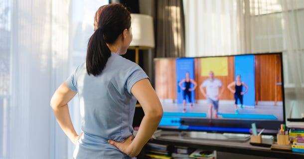 Donna segue corso di fitness a casa tramite smart tv