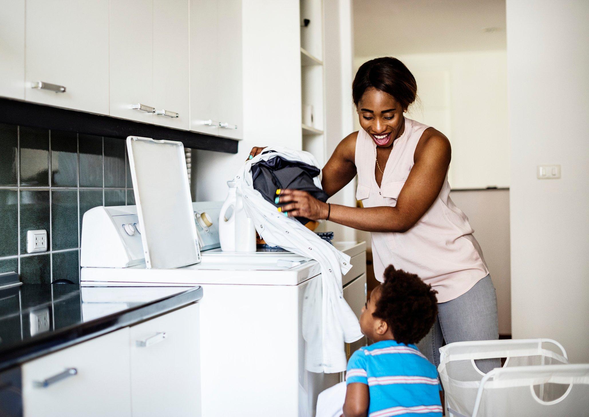Mom helping son do laundry