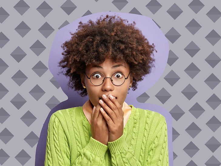 Woman looking surprised and covering her mouth with her hands.