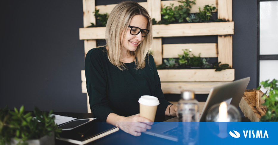 Investment Manager  working at a sustainable office looking at her laptop while holding a cup of coffee