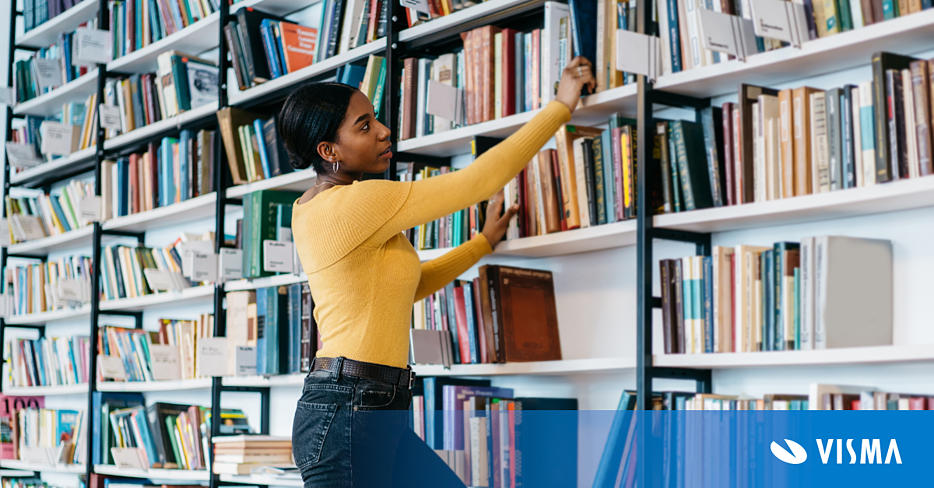 Young  woman in casual outfit taking textbook from bookcase  in library of modern university