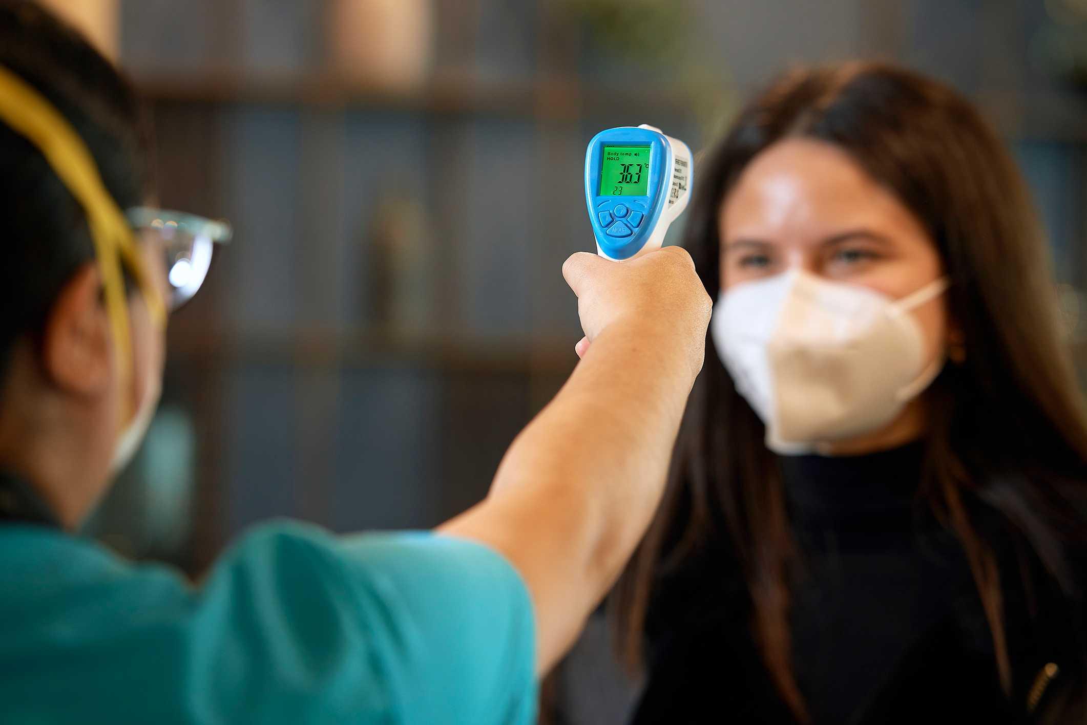 enfermera tomando la temperatura de un visitante