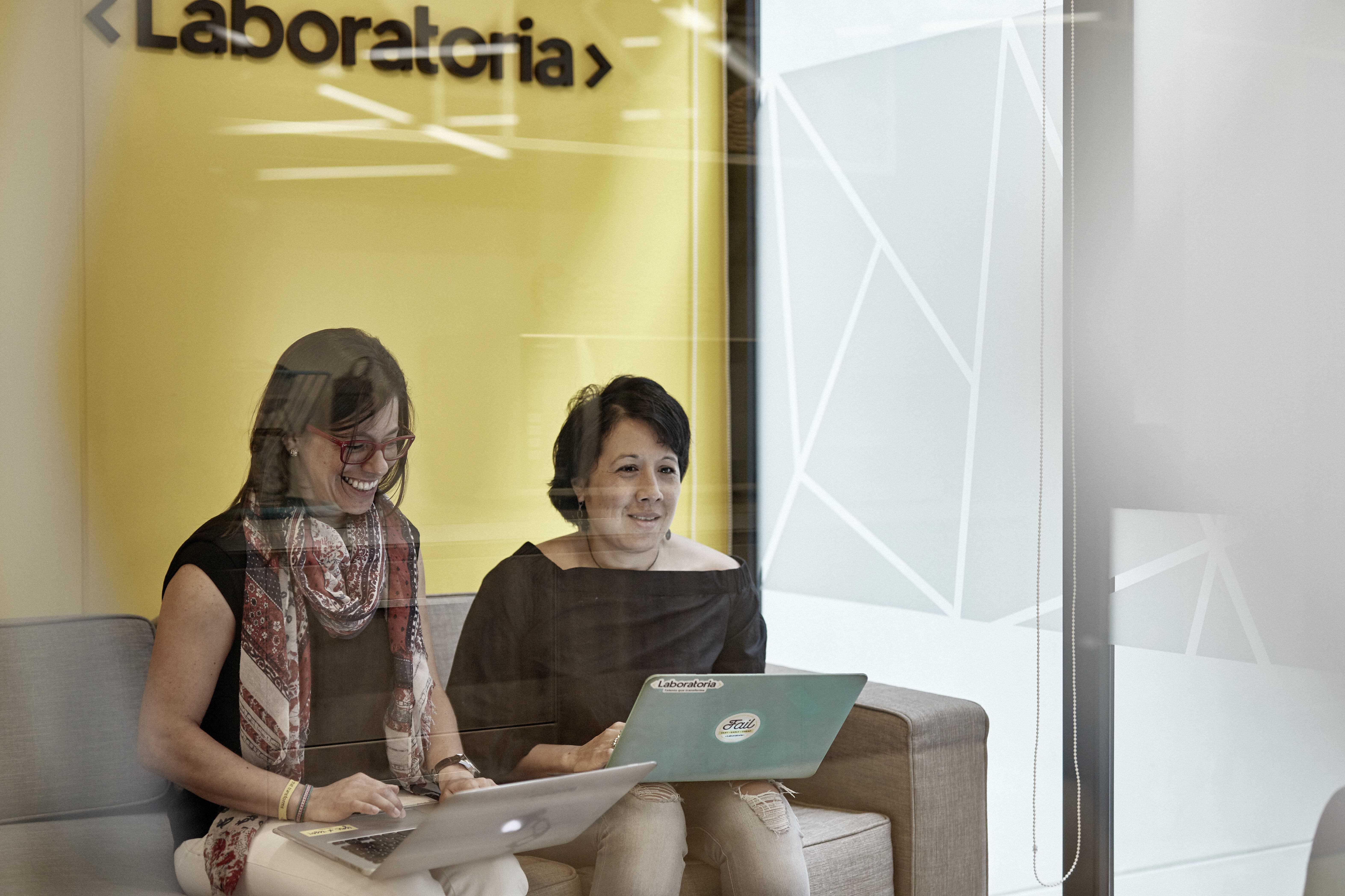 dos mujeres de laboratoria conversando en una oficina