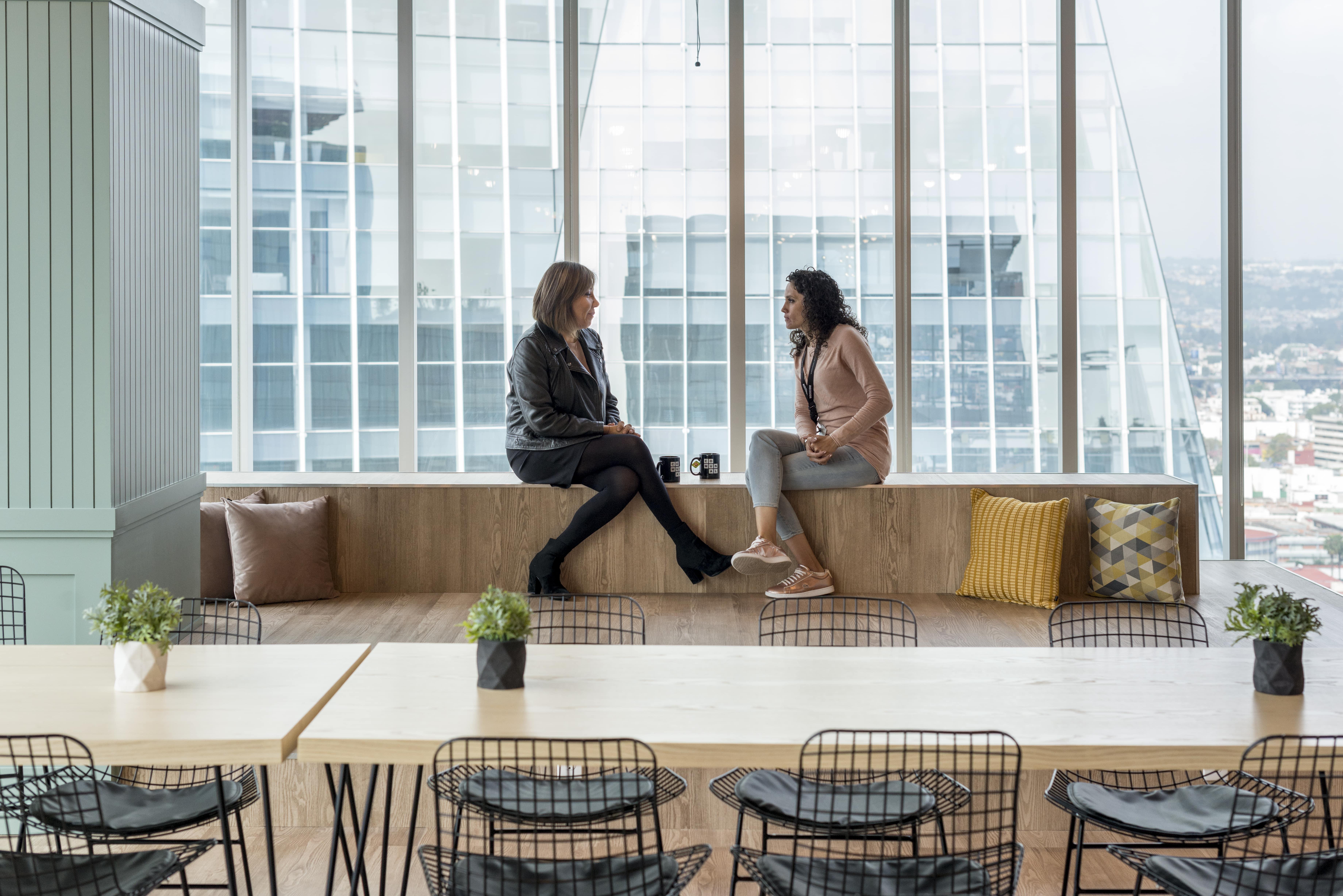 dos personas conversando en un comedor dentro de un coworking