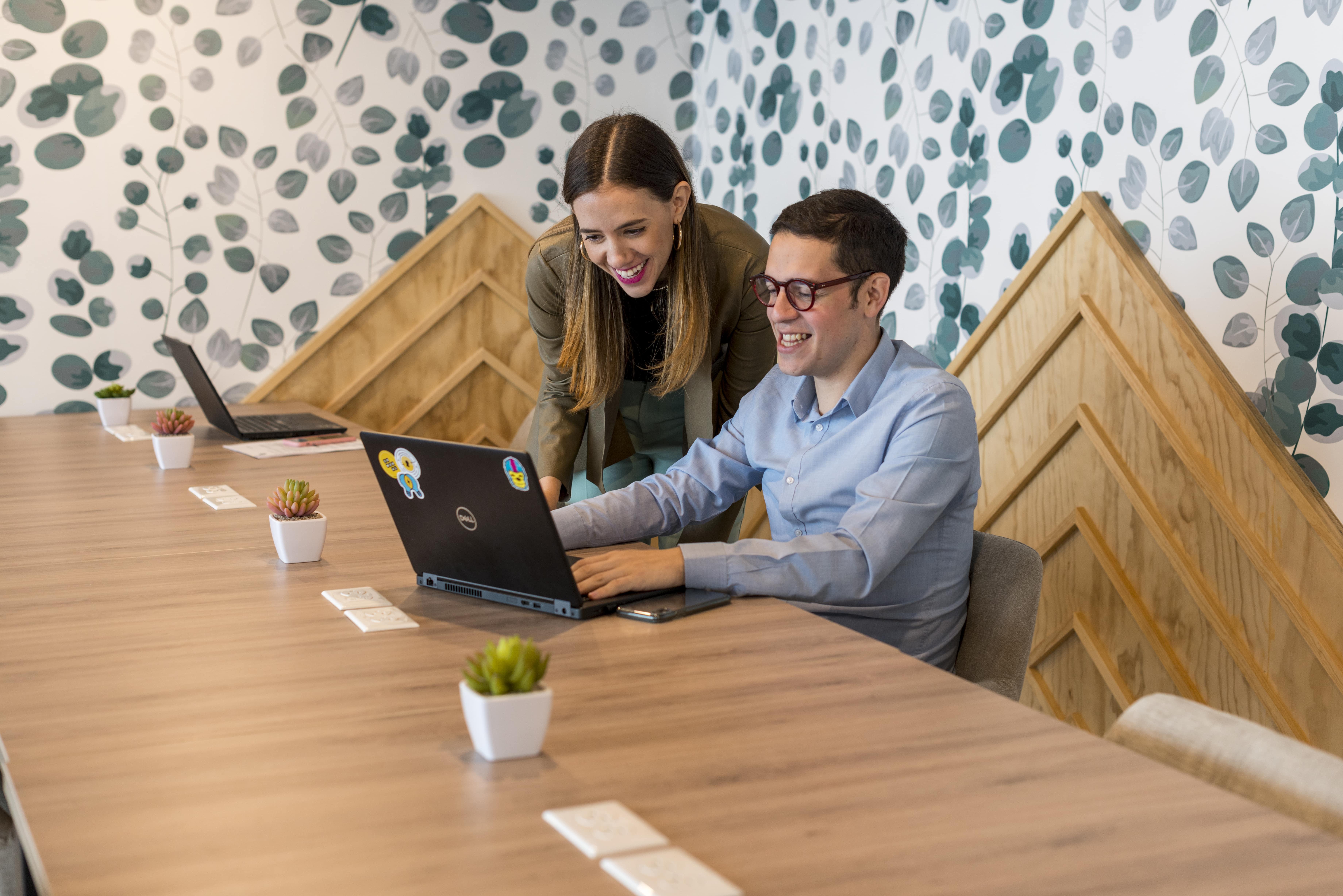 dos sonrientes colaboradores revisando una laptop en una oficina