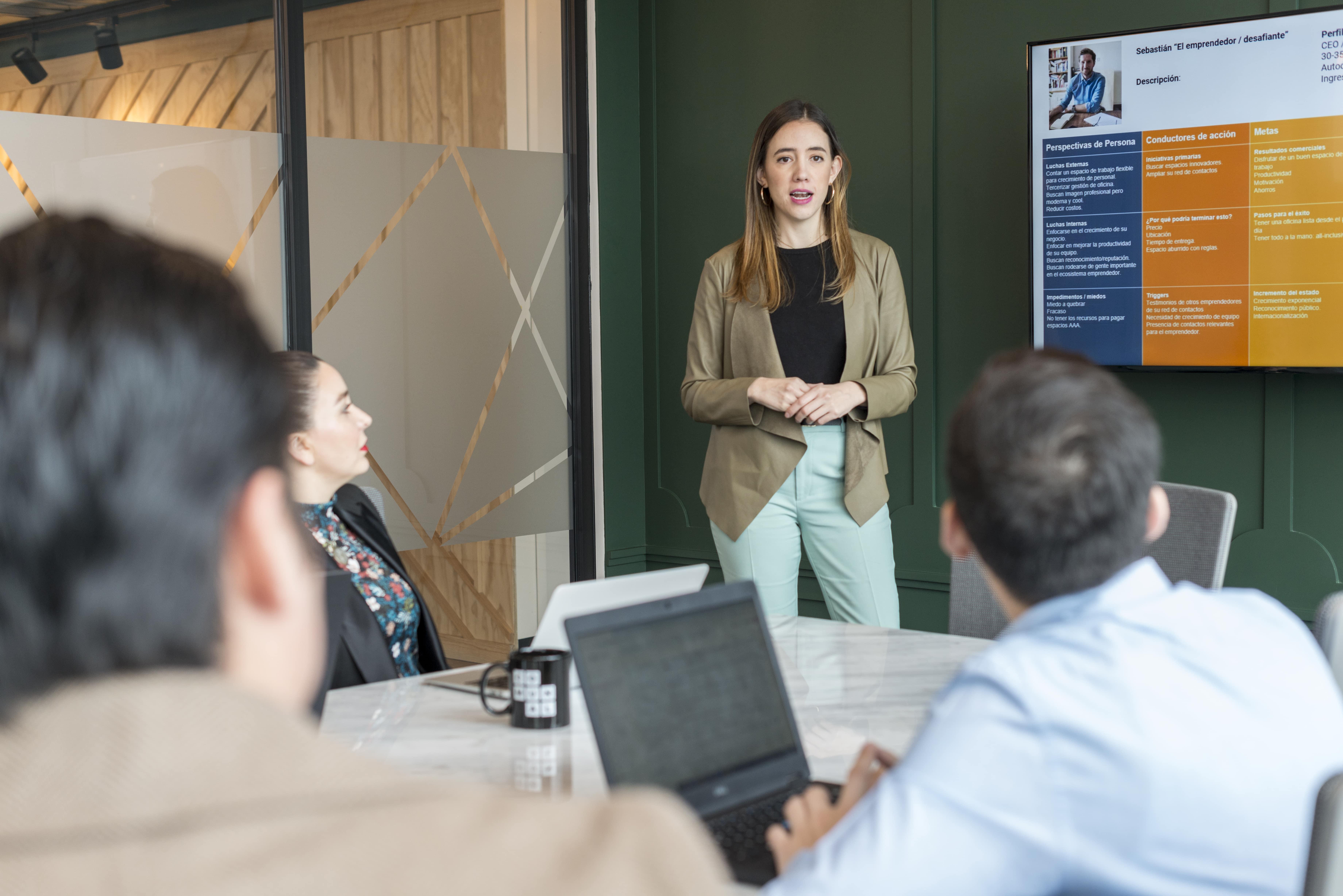 mujer exponiendo en una reunion frente a su equipo