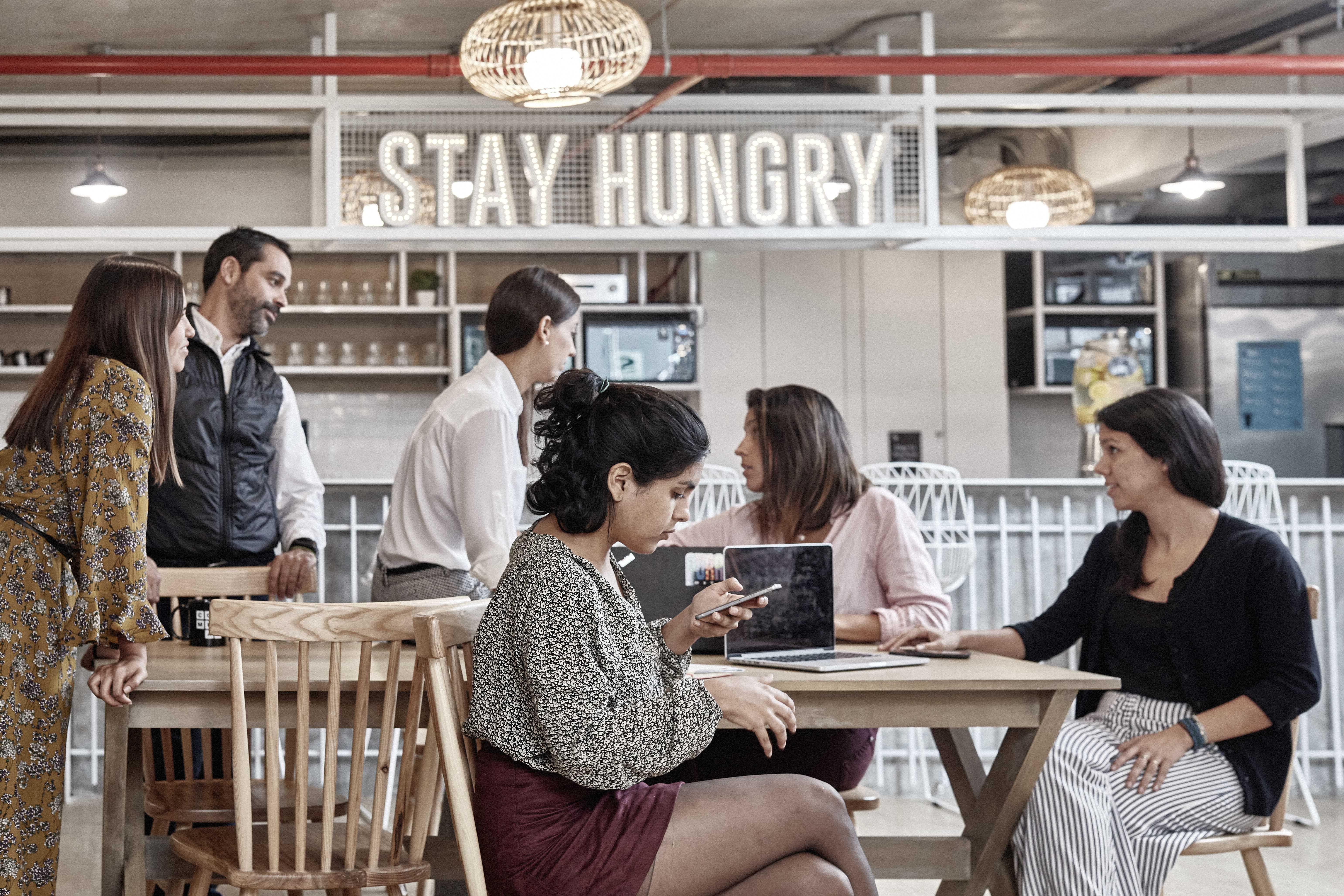 personas conversando en una cafeteria de un coworking