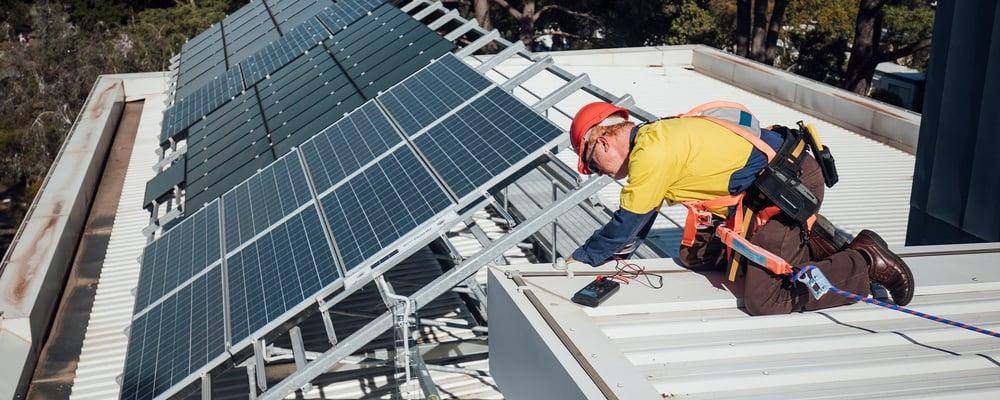 Mies katolla asentamassa aurinkopaneeleja.