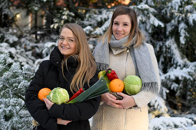 Tuulia Järvinen Venneriltä ja Hanna Siimes POP Pankilta pitelevät sylissään kasviksia, jotka sisältyvät Vennerin ruokalaatikkoon.