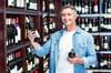Smiling man holding bottles of wine in supermarket