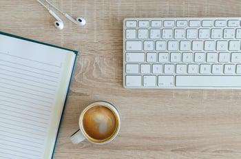 notebook, headphones, mug, and keyboard on table