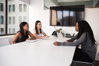 three women in an interview setting