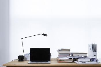 Tablet on desk with stack of books