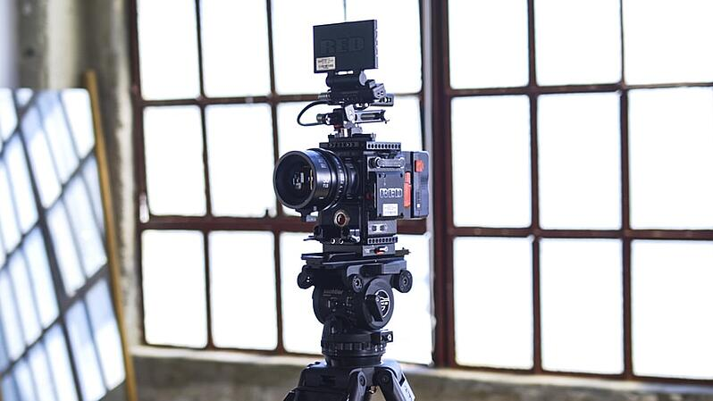Camera on tripod for creating videos of portfolio managers