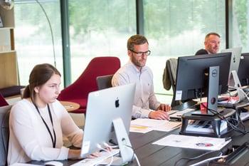 Business professionals working on desktop monitors