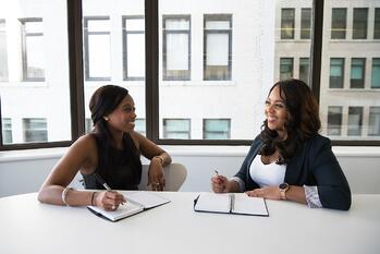 Two women talking business at table