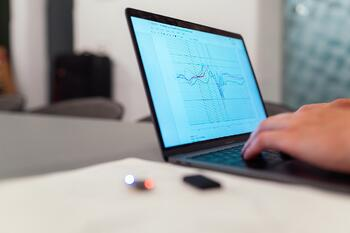 hand on a laptop that shows data