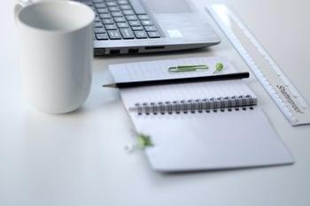 planner, pen, mug, and laptop on desk