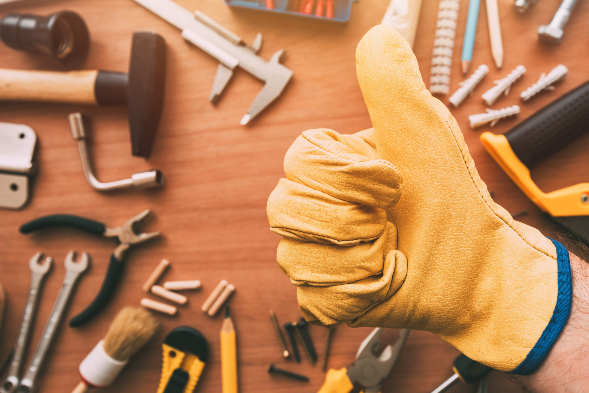 Maintenance handyman gesturing thumb up approval hand sign over the work desk with DIY tools, top view
