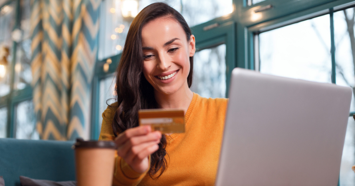 Woman holding her credit card while learning about the payment methods offered by Billforward
