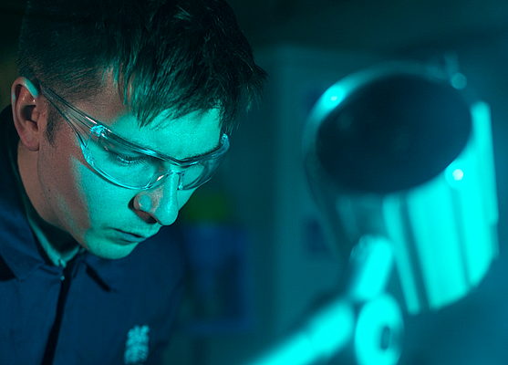 Must-have modern workplace tools to secure your organisation from data loss - man wearing goggles working in a blue-lit environment