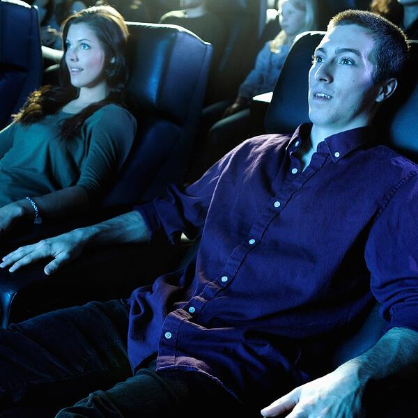 A woman and a man are seated in a movie theater