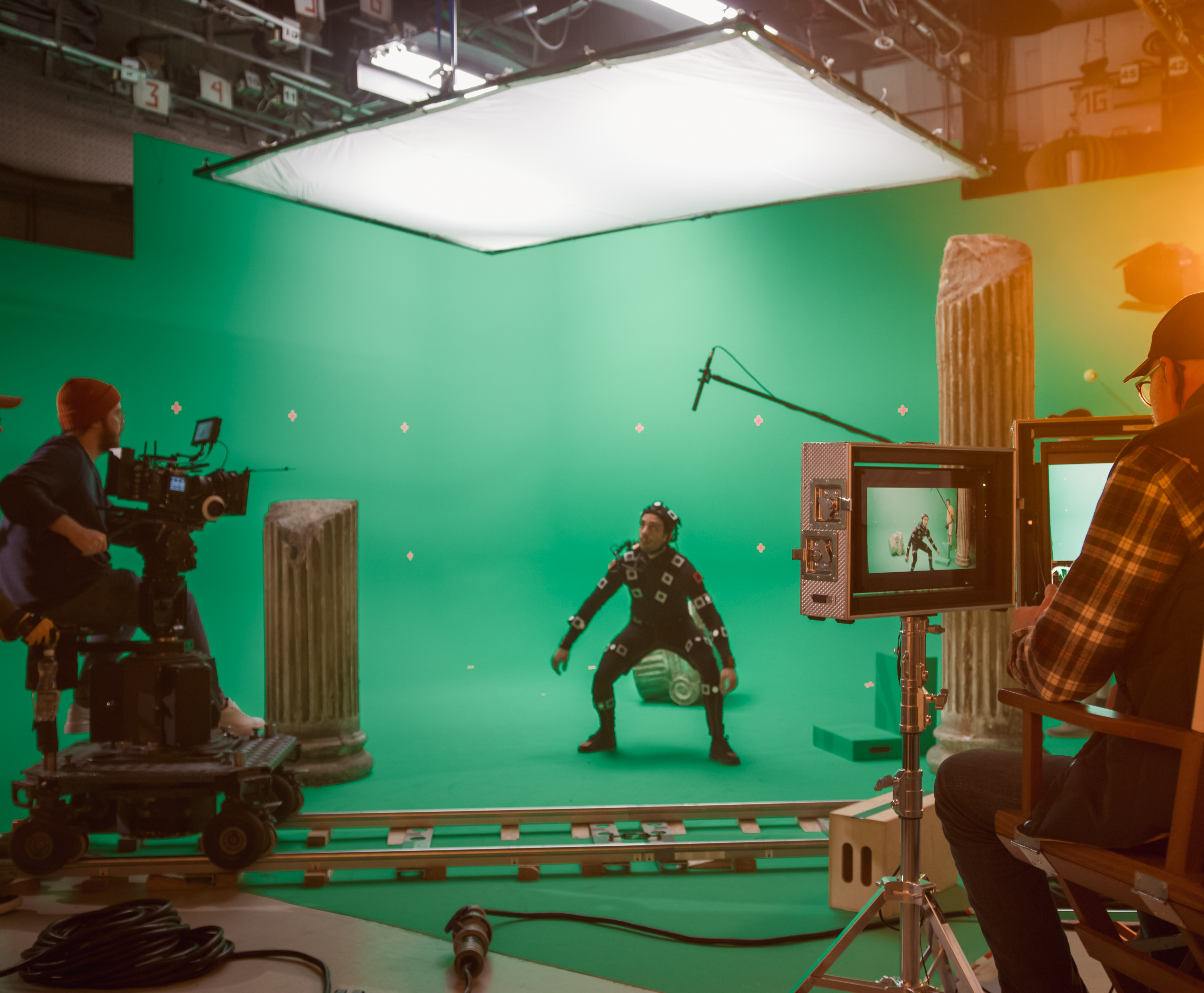 In-the-Big-Film-Studio-Professional-Crew-Shooting-Blockbuster-Movie.-Director-Commands-Cameraman-to-Start-shooting-Green-Screen-CGI-Scene-with-Actor-Wearing-Motion-Capture-Suit-and-Head-Rig-1265157445_5120x2880