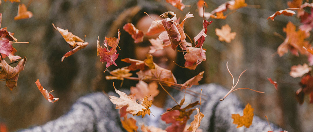 african american girl throwing leaves in fall