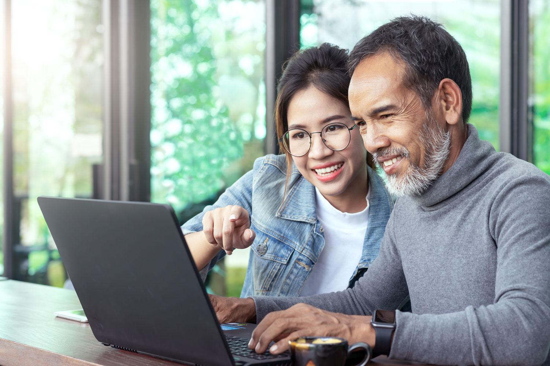 joven ayudando a adulto mayor a usar computadora