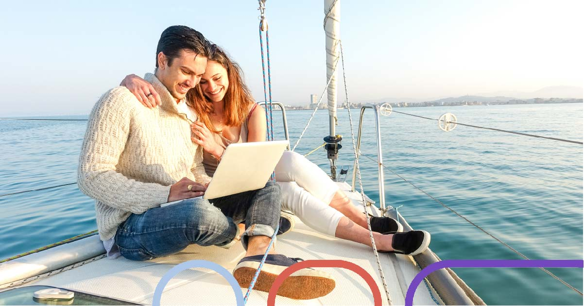 Two people sit on their laptop on a yacht