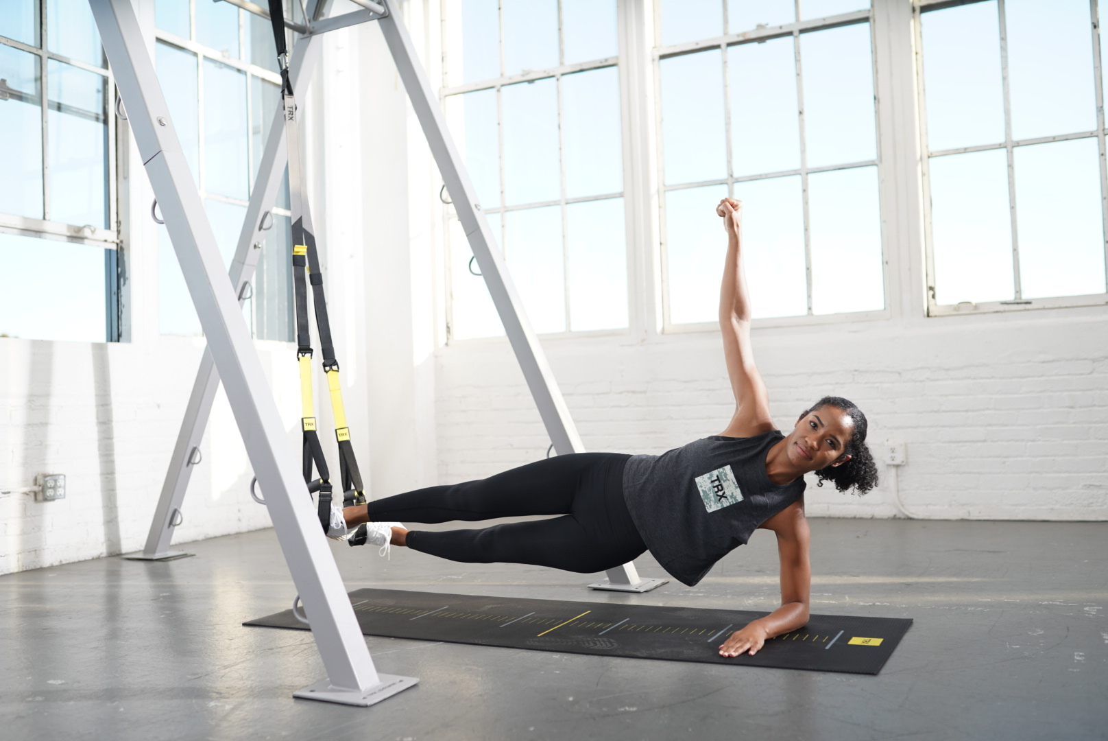 woman in trx side plank with arm up in digicamo cropped tank in a studio space