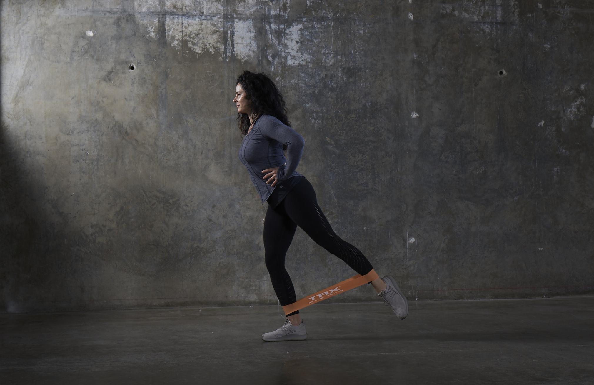 TRX exercise bands in gym grey studio female single leg kick back