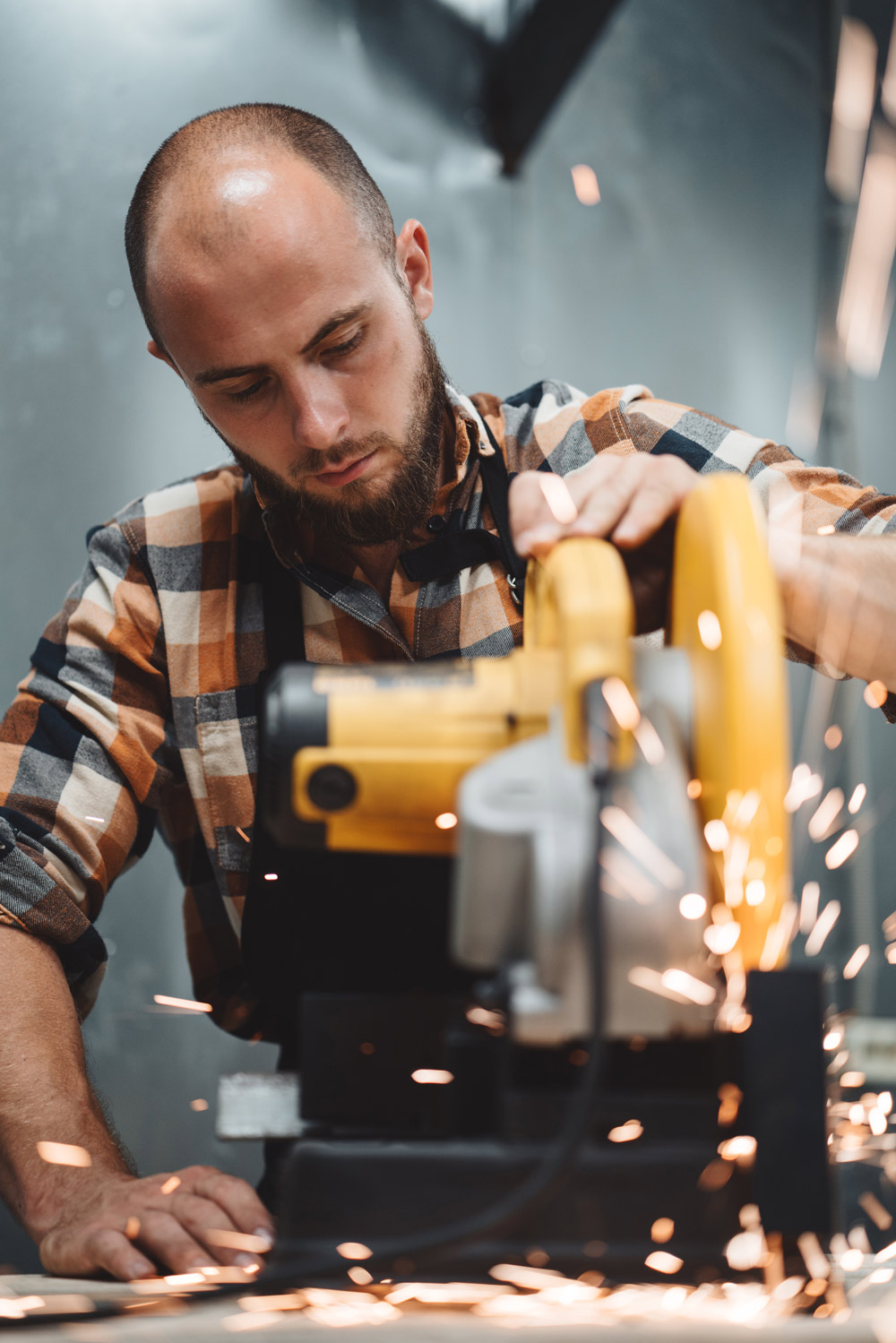 Canva---Bearded-worker-mechanic-using-electrical-angular-grinding-machine-in-metalworking.-Work-in-action.-Sparks-fly-apart